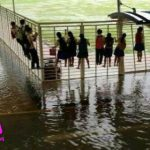 Fairfield Methodist Secondary students clinging to a fence to avoid rising flood waters.