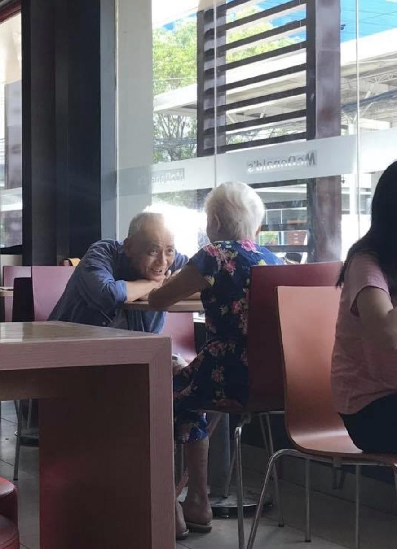 Elderly man gazing fondly at his elderly date in McDonald's